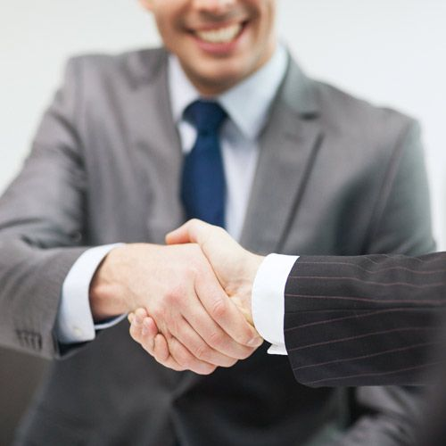 close up of two business men wearing suits shaking hands